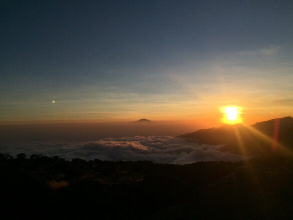 Sun setting above the cloud layer looking out over Mount Mawenzi